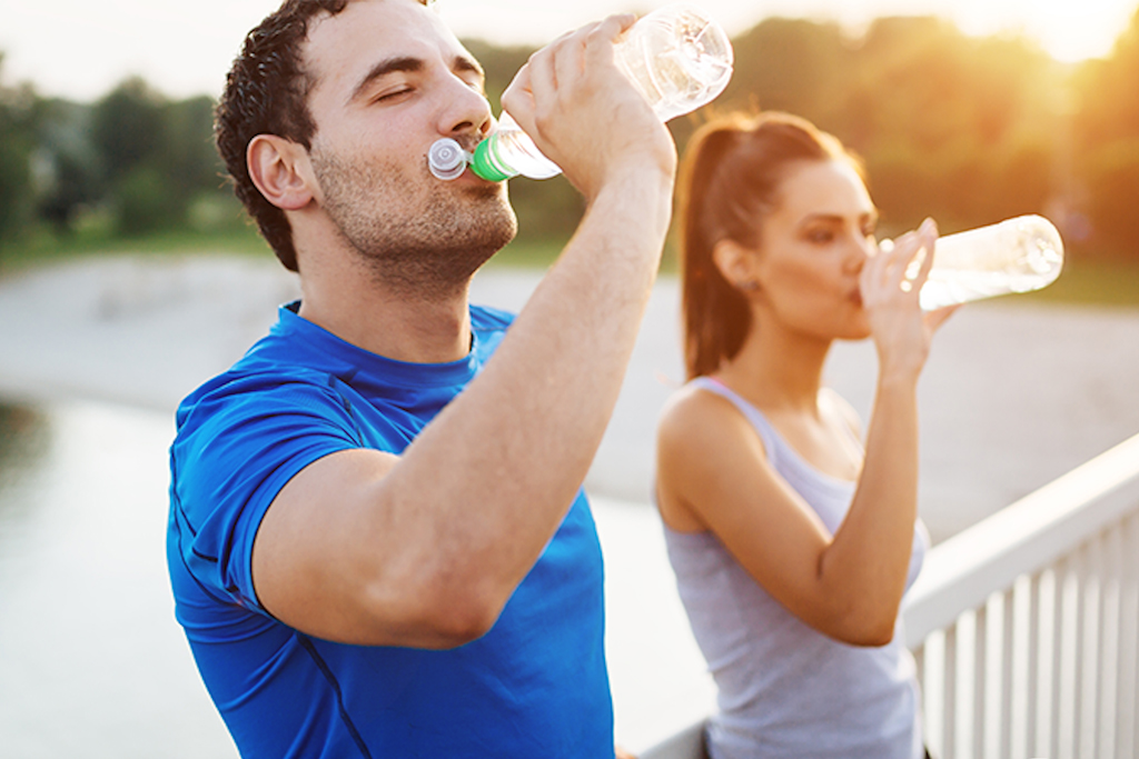 Herbalife Nutrition fitness couple drinkg water while exercise hydration