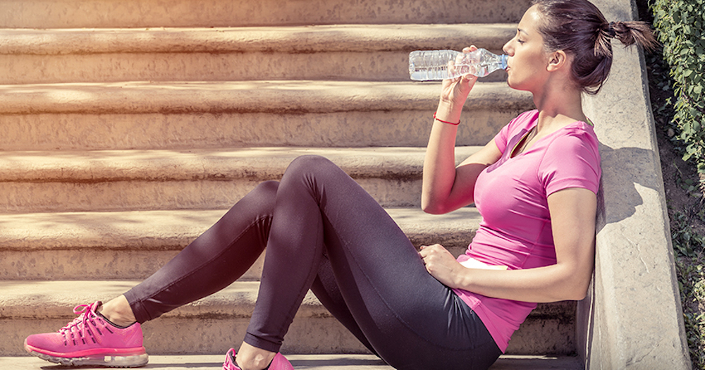 Fitness woman drinking water sitting on stairs